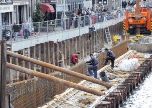 Aan de Amsterdamse Prinsengracht werken betonvlechters aan de bekisting voor een nieuw gedeelte van de walmuur.