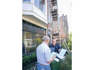 """Inspecteur Baneman waarschuwt zelfstandig ondernemer Tom Cahill: """"De afstand tussen werkvloer op de steiger en de gevel is plaatselijk meer dan 15 centimeter. Die gedeelten moeten worden beveiligd.""""Foto: Peter van Mulken"""