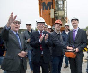 Met hulp van een kraanmachinist hijst minister Blok een bouwdoek omhoog als officiële opening van de Dag van de Bouw. Bouwend Nederland-voorzitter Elco Brinkman (links) en De Raad-directeur Paul Brandjes kijken toe.
