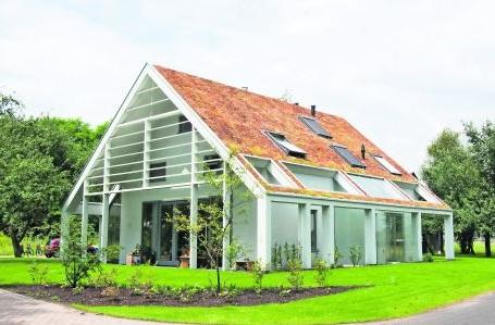 Woning en bijgebouw met houten glasvliesgevels en massief hout