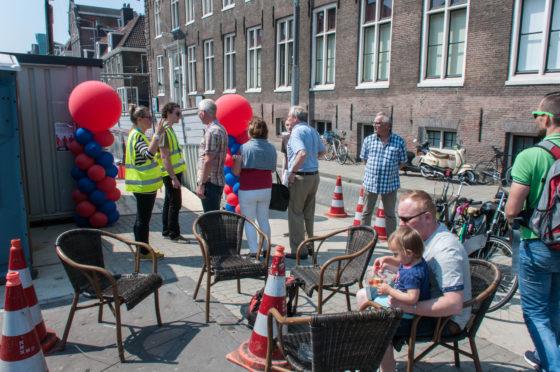 Gemoedelijk wachten in het zonnetje voor station Vijzelgracht in Amsterdam