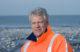 Portret deltacommissaris in oranje windjack met zee op achtergrond groot 80x52