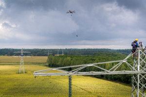 Drone spant draden tussen hoogspanningsmasten